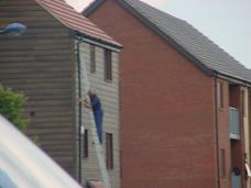 Workman up a ladder on a three storey building