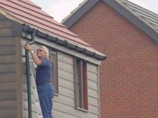 Working at the top of a ladder on a three storey building